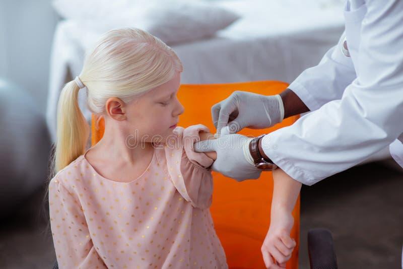 Manipulera att desinficera hud efter injektionen för gullig flicka royaltyfria bilder