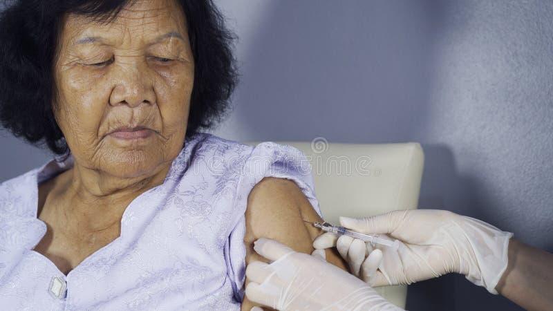 Manipulera att ge den vaccinera injektionen in i hög kvinna royaltyfria bilder