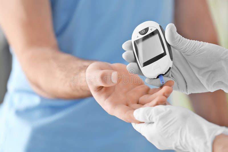 Manipulera att kontrollera den diabetiska tålmodiga för blodsocker för ` s nivån royaltyfria foton
