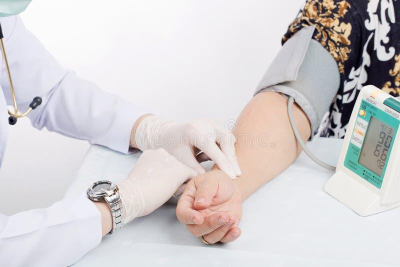 Manipulera att kontrollera puls av patienten med stetoskopet på tabellisolator royaltyfri bild