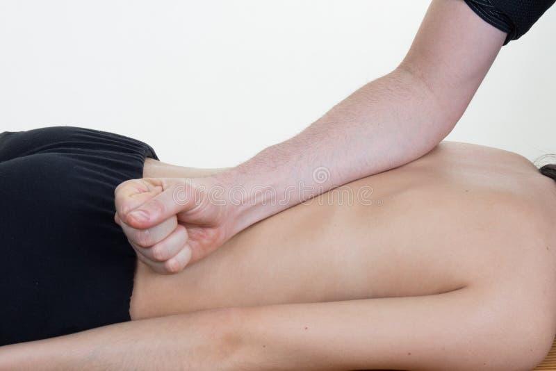 Manipulera att massera baksidan av hans patient, medan genom att använda baksidan royaltyfri foto