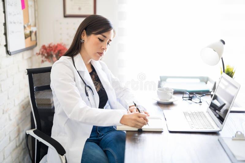 Manipulera att skriva ett medicinskt recept på en bok royaltyfri bild