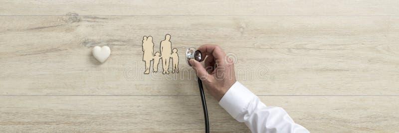 Manipulera den hållande medicinska stetoskopet över ett snitt ut ur en familj royaltyfri bild