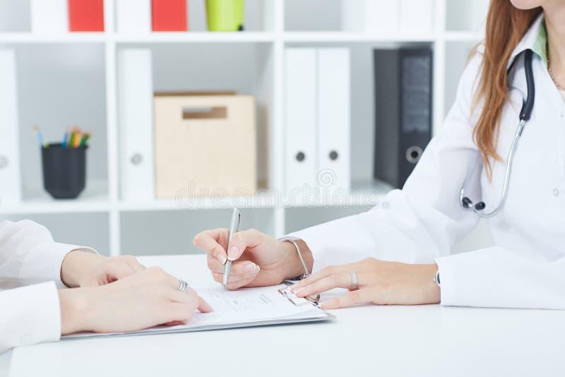 Manipulera explaning till hennes kvinnliga patient hur man fyller den medicinska formen på kontoret royaltyfria foton