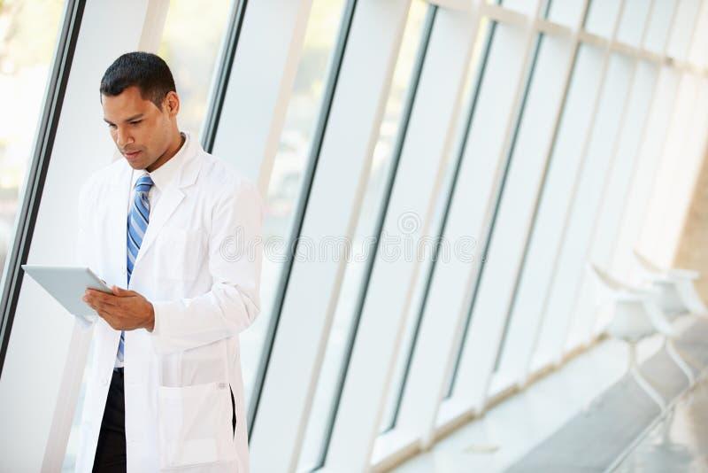 Manipulera genom att använda den Digital tableten i korridor av det moderna sjukhuset arkivfoton
