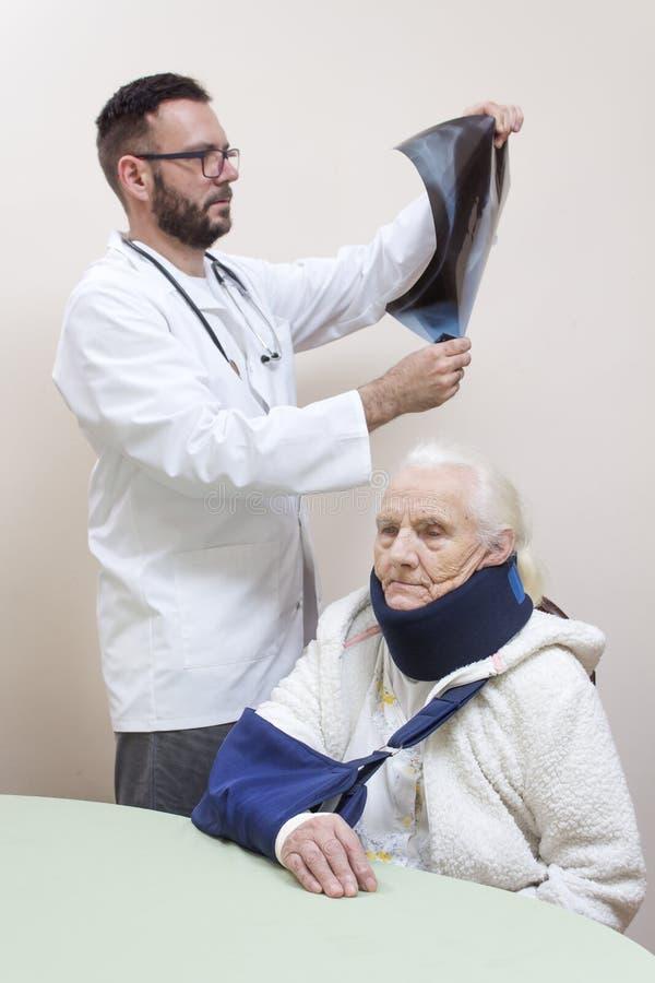 Manipulera i ett vitt lag håller ögonen på en röntgenstrålebild En gammal gråhårig kvinna sitter på en stol med en rem på hennes  arkivfoton