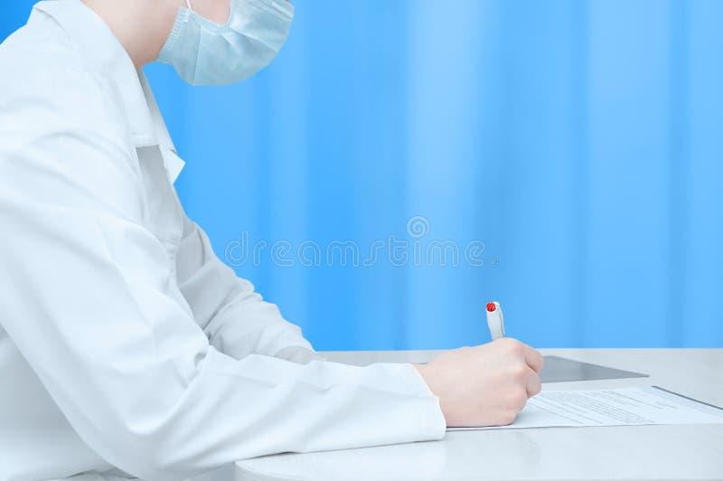 Manipulera i ett vitt lag sitter på tabellen och undertecknar dokumentet royaltyfria bilder