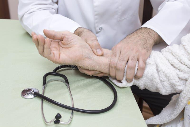 Manipulera i ett vitt lag undersöker pulsen på handleden av en gammal kvinna i en vit badrock Stetoskopet är på tabellen arkivbilder