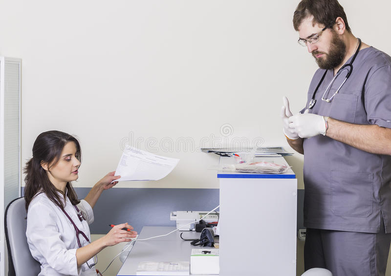 Manipulera kvinnasammanträde på en tabell, en manlig doktor är på sjukhuset med dokument royaltyfri fotografi