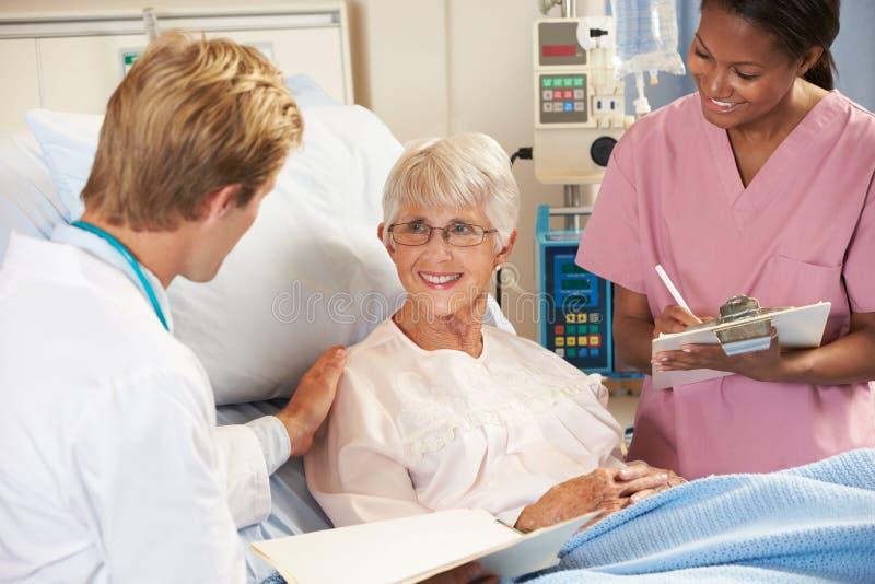 Manipulera med sjuksköterskan som talar till hög kvinnlig tålmodig i säng arkivfoto