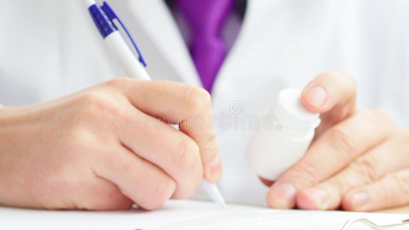 Manipulera sammanträde på worktablen som rymmer flaskan av preventivpillerar och skriver receptet fotografering för bildbyråer