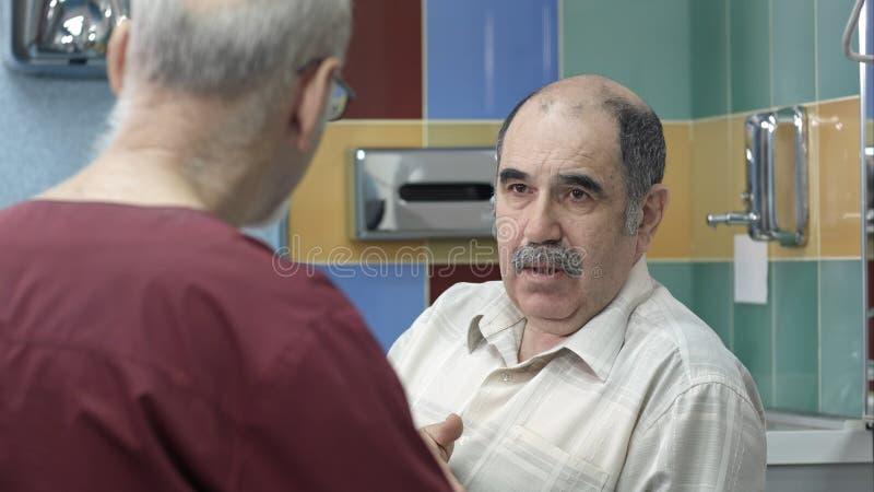 Manipulera samtal till den höga manliga patienten på kontoret arkivfoto