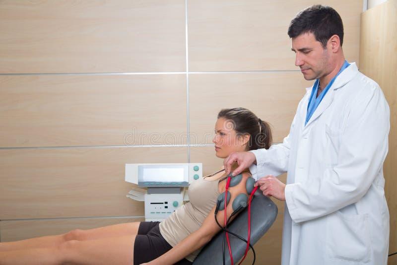 Manipulera terapeuten som kontrollerar muskelelectrostimulation till kvinnan royaltyfria bilder