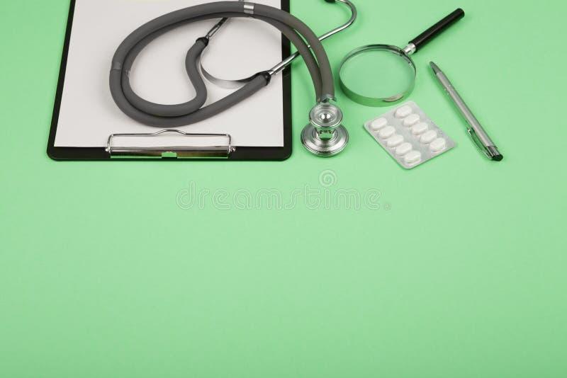 manipulerar arbetsplatsen - medicinsk minnestavla, stetoskop, preventivpillerar och förstoringsglas arkivbild