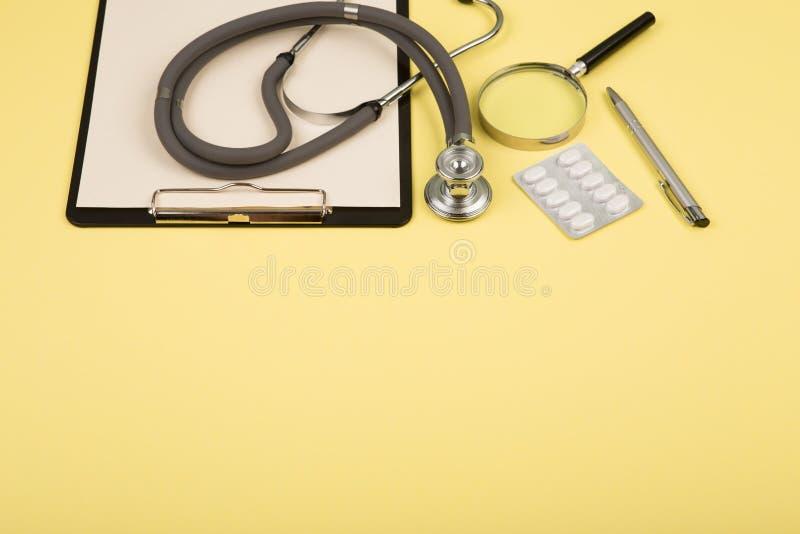 manipulerar arbetsplatsen - medicinsk minnestavla, stetoskop, preventivpillerar och förstoringsglas royaltyfri bild