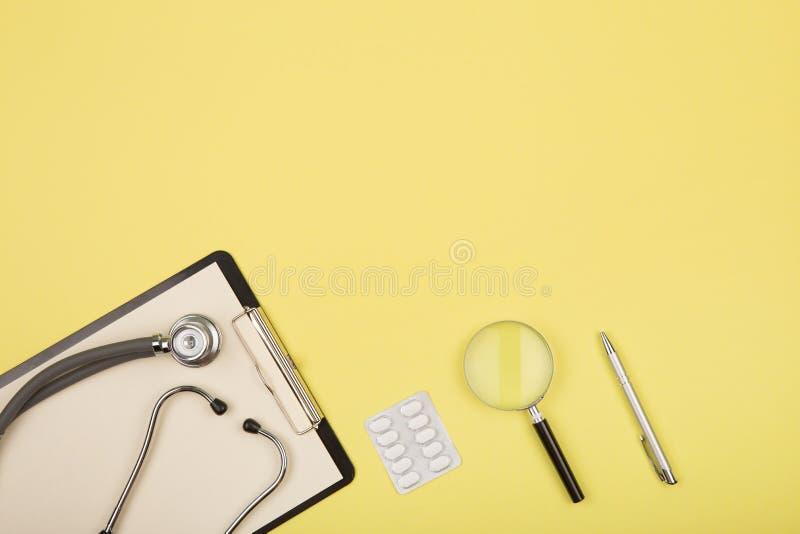 manipulerar arbetsplatsen - medicinsk minnestavla, stetoskop, preventivpillerar och förstoringsglas royaltyfri fotografi