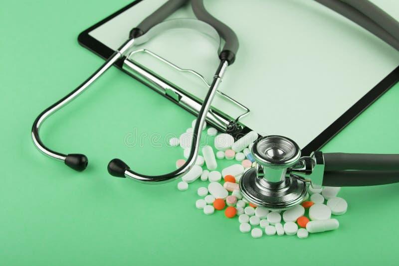 manipulerar arbetsplatsen - medicinsk minnestavla, stetoskop, preventivpillerar och f?rstoringsglas arkivbild