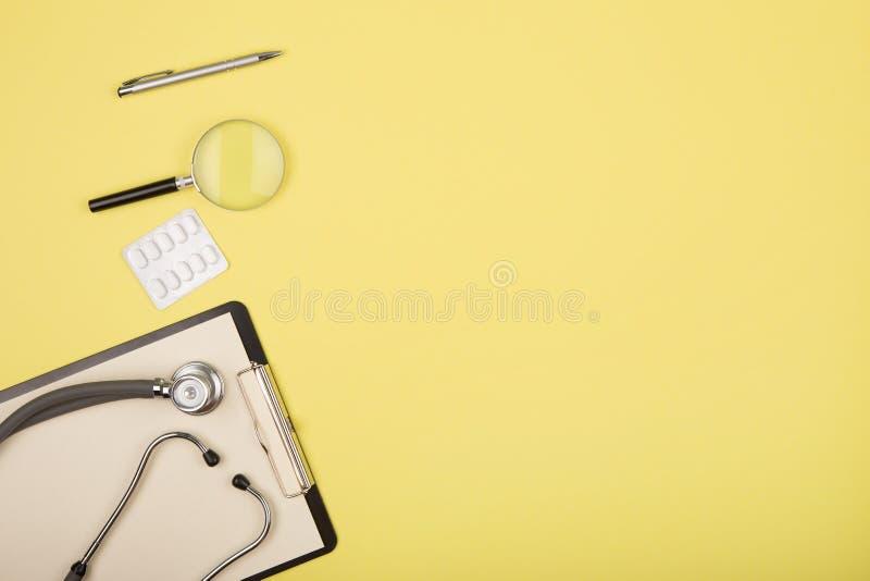 manipulerar arbetsplatsen - medicinsk minnestavla, stetoskop, preventivpillerar och f?rstoringsglas fotografering för bildbyråer