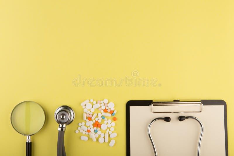 manipulerar arbetsplatsen - medicinsk minnestavla, stetoskop, preventivpillerar och f?rstoringsglas arkivfoton