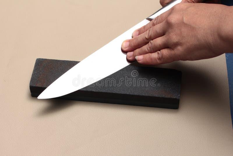 Manipulez le couteau pour faire un couteau pointu avec de la pierre à aiguiser photo stock