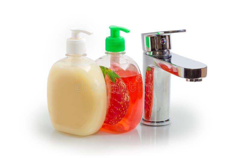 Manipulez le robinet de mélangeur et deux bouteilles différentes de savon liquide photo libre de droits