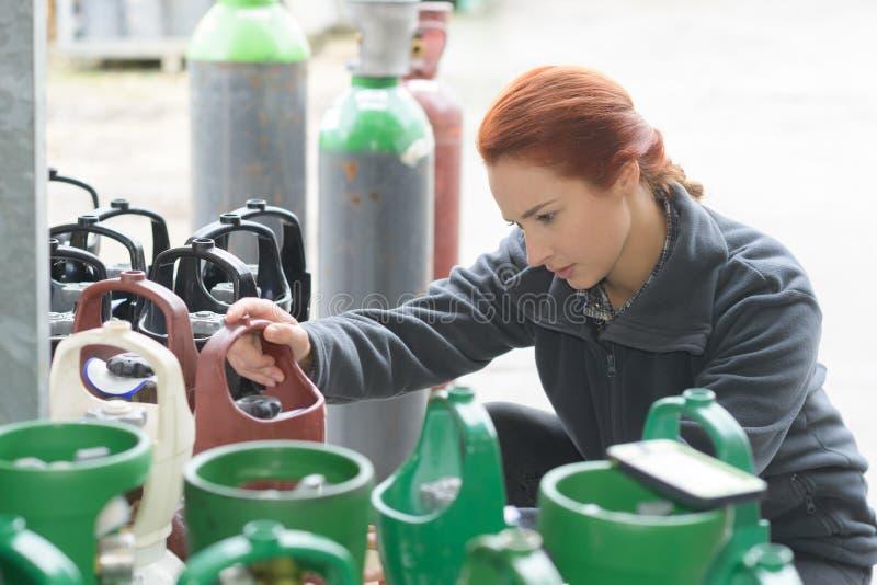 Manipulierungssauerstoffflaschen der jungen Frau stockbild