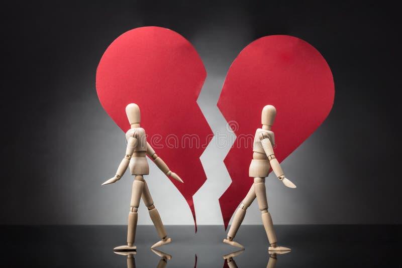 Maniquí de madera dos que se coloca cara a cara con el corazón quebrado fotografía de archivo