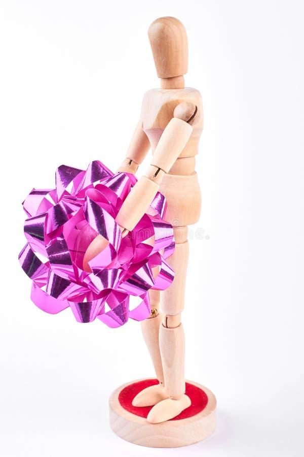 Maniquí de madera que lleva a cabo el arco rosado fotografía de archivo libre de regalías