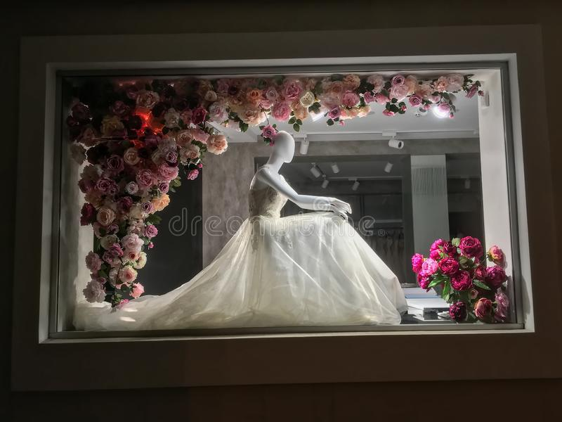 Maniquí en un vestido de boda, en la noche en una ventana de la tienda vestida fotografía de archivo