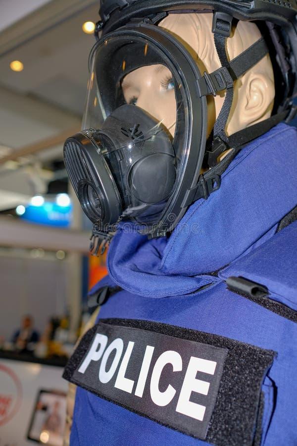 Maniquí en uniforme de la policía y máscara de la seguridad que lleva imagenes de archivo
