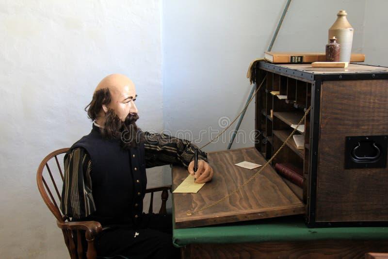 Maniquí masculino que se sienta en el escritorio, escribiendo letras a la familia durante reconstrucciones de la guerra, fuerte O fotos de archivo libres de regalías