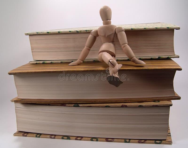 Maniquí que se sienta en los libros