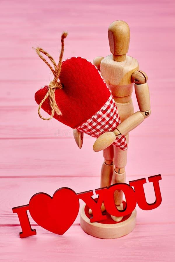 Maniquí simulado de madera en el amor que lleva a cabo el corazón imágenes de archivo libres de regalías