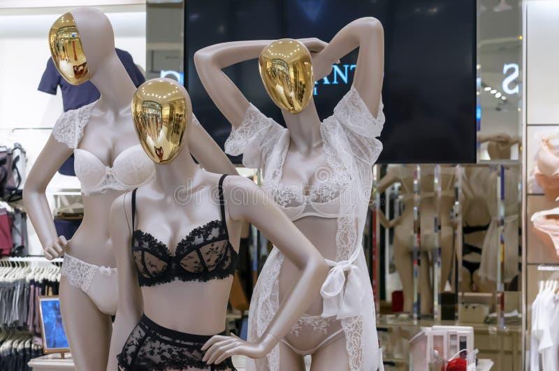 Maniquíes femeninos con las caras del oro en ropa interior de encaje imagenes de archivo