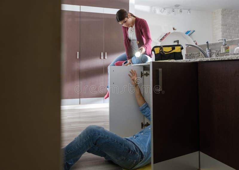 Manitas Husband y esposa que repara el fregadero de cocina imágenes de archivo libres de regalías