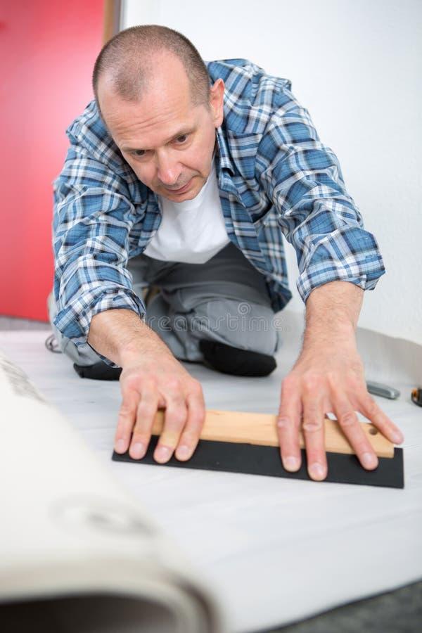 Manitas que instala el nuevo entarimado de madera acodado foto de archivo