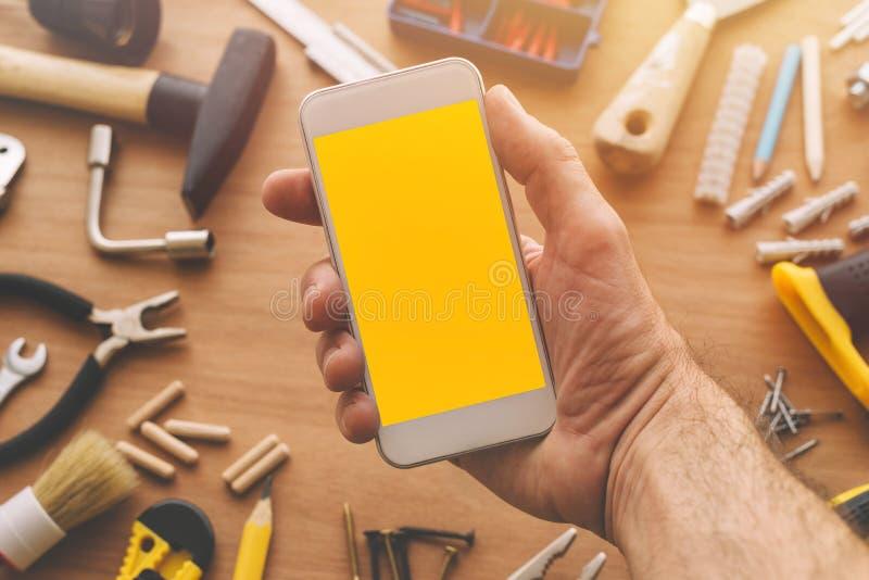 Manitas que sostiene el teléfono elegante con la pantalla en blanco a disposición fotografía de archivo libre de regalías
