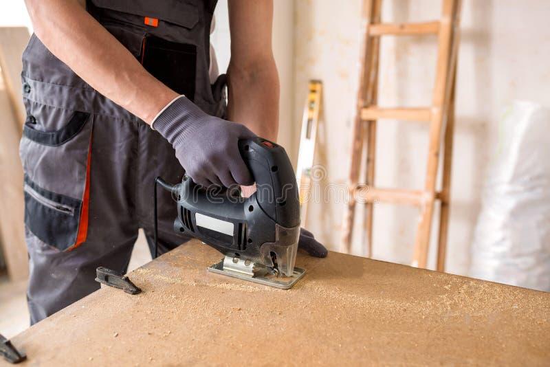 Manitas que usa una sierra de la plantilla para el trabajo de la carpintería fotografía de archivo