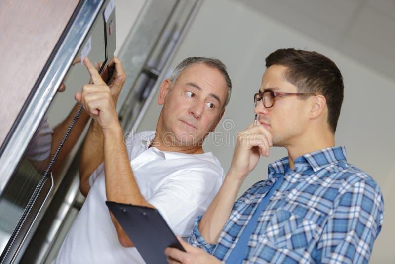 Manitas y compañero de trabajo que comprueban el refrigerador con la linterna en casa imagenes de archivo