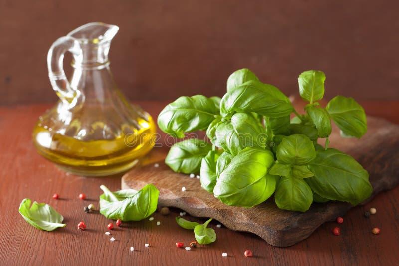 A manjericão fresca deixa a erva e o azeite no bacgkround de madeira foto de stock