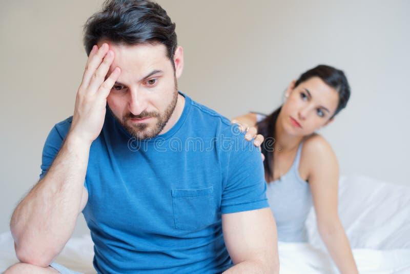 Mankänsla som är generad och som är otrygg i sängen royaltyfri foto