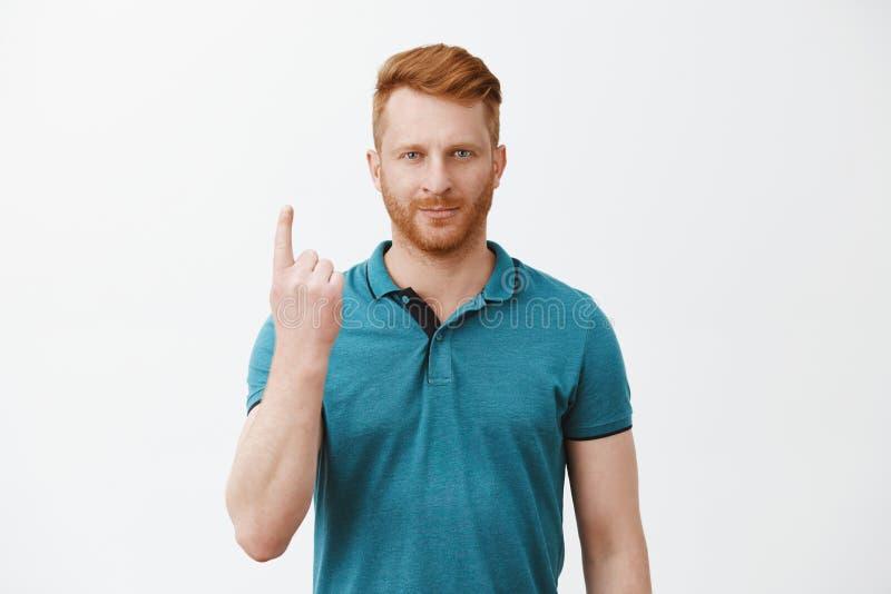 Mankänsla som nummer ett Stående av den säkra stiliga rödhåriga mannen med borstvisningpekfingret som att räkna arkivfoto