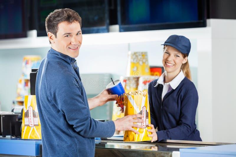 Manköpandepopcorn och drink från säljare på royaltyfria foton