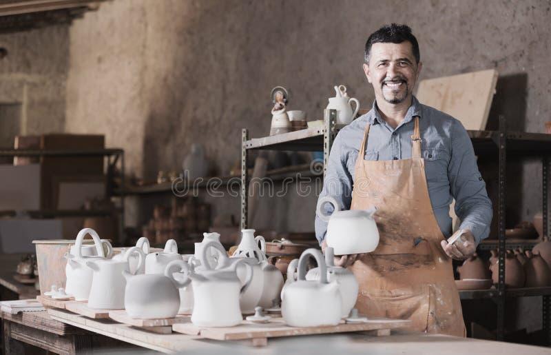 Mankeramiker som rymmer keramiska skyttlar i atelier royaltyfria bilder