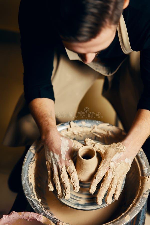 Mankeramikerarbete på keramikerhjulet som gör den keramiska krukan från lera i krukmakeriseminarium arkivbilder