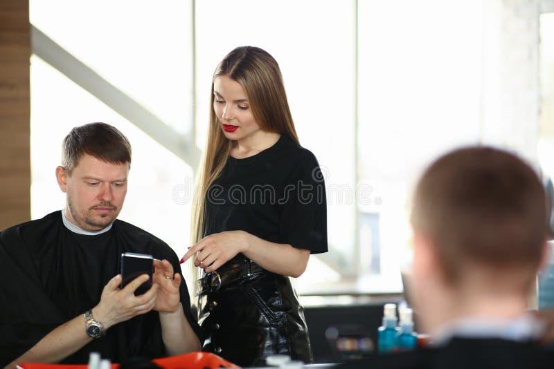 Manklientvisning på telefonen till kvinnafrisören arkivfoton