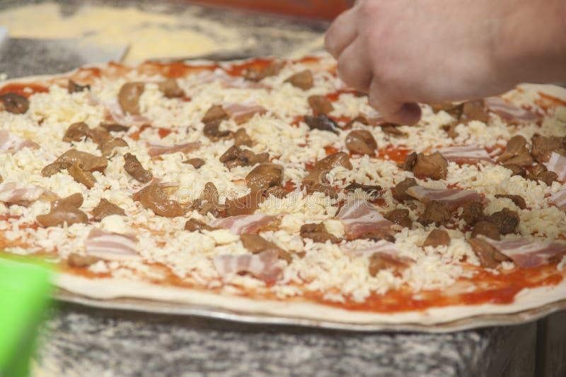 Mankock med rå pizza royaltyfri foto
