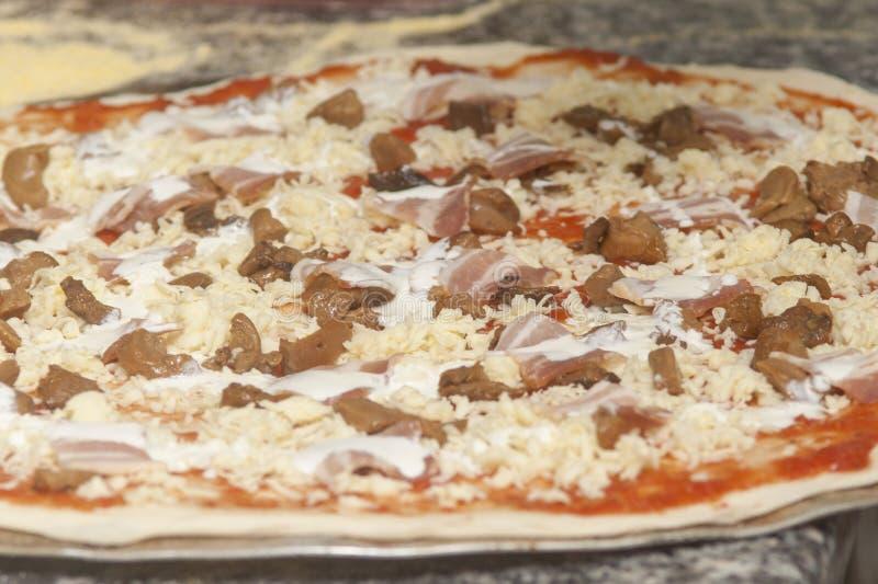 Mankock med rå pizza arkivbild