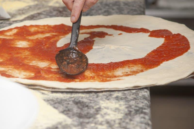 Mankock med rå pizza arkivfoto