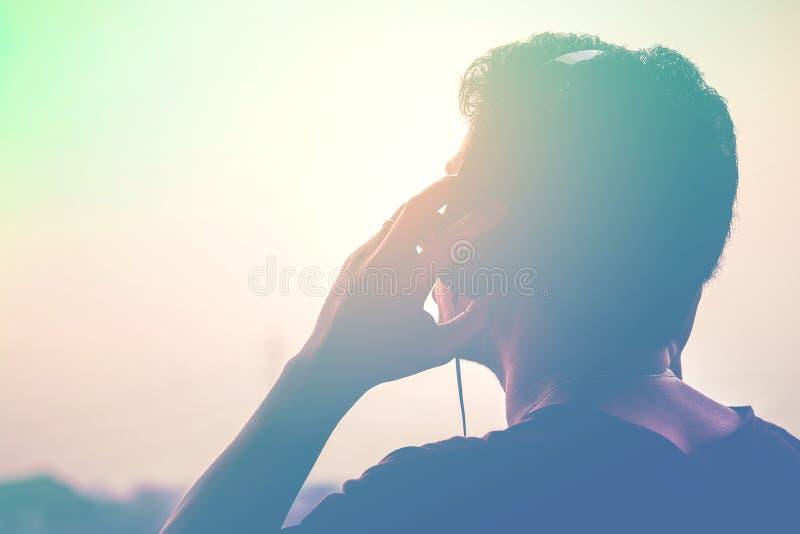 Mankontur som lyssnar till hörlurar på solnedgånglandskapbakgrunden arkivbilder